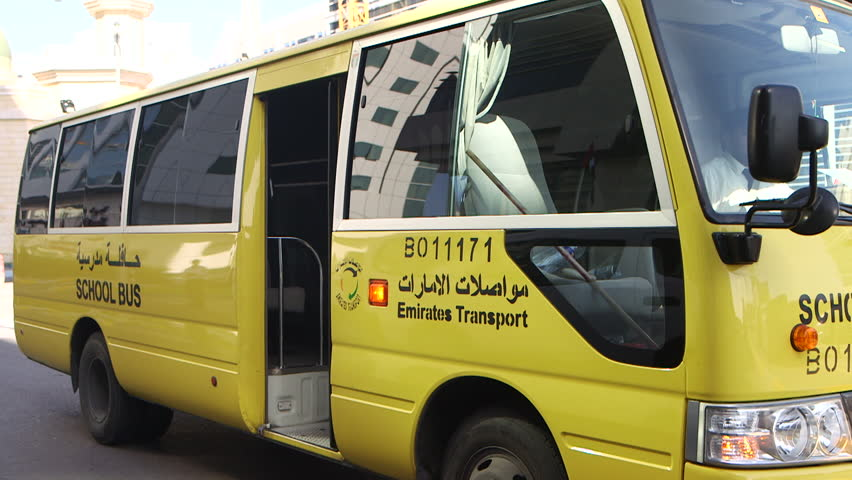 Yellow school bus. Side view of a parked yellow school bus with side lettering on the bus in English and Arabic. Automatic door closes. (Abu Dhabi - UAE-2013) | Shutterstock HD Video #18736934