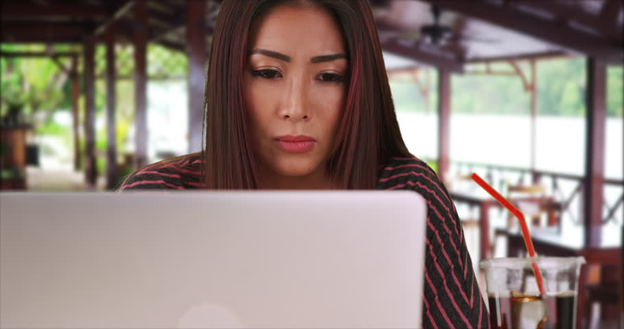 Serious Japanese woman working on laptop in restaurant   Shutterstock HD Video #18920597