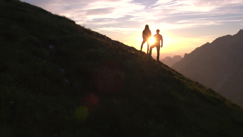 Aerial - Rising above hiking couple celebrating successful climb on the mountain with raising arms at beautiful sunset | Shutterstock HD Video #18955652