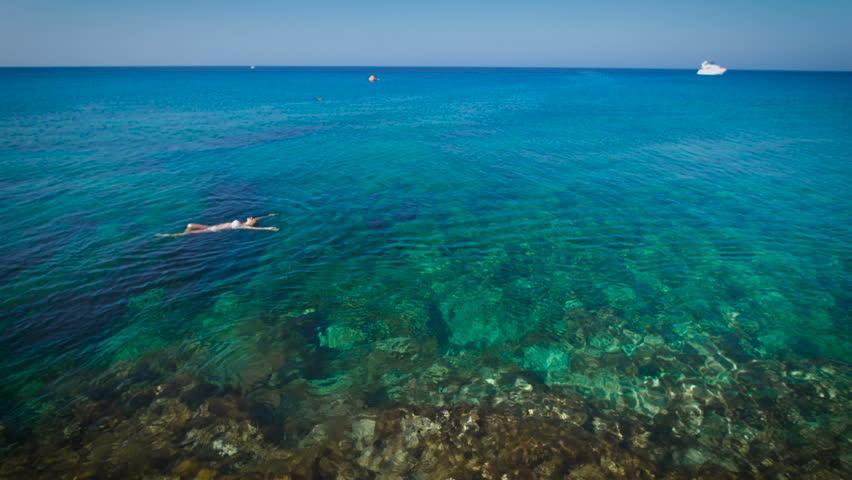 Young woman swimming in beautiful azure sea | Shutterstock HD Video #18957785