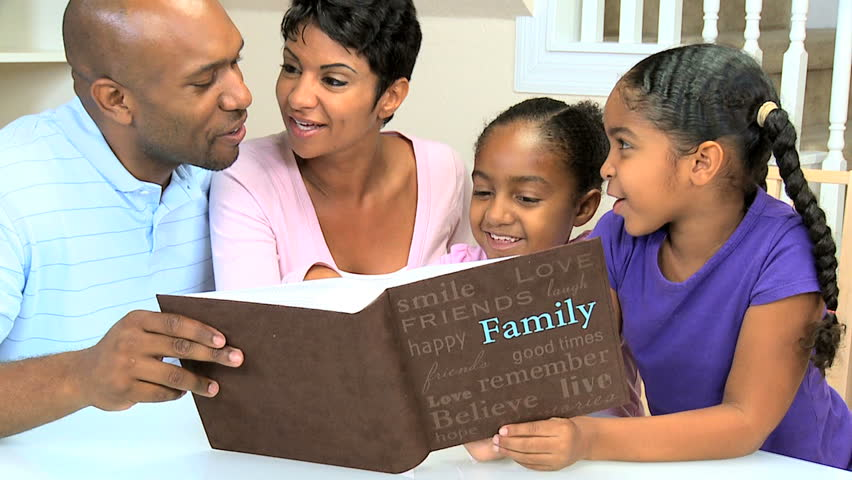 Young ethnic parents and children enjoying the family photograph album - HD stock footage clip