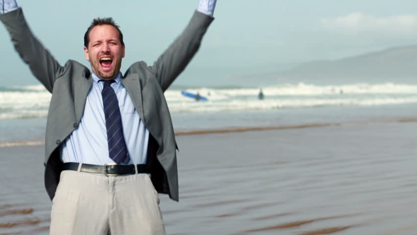 Excited businessman screaming and raising hands to the sky by the sea, slow motion