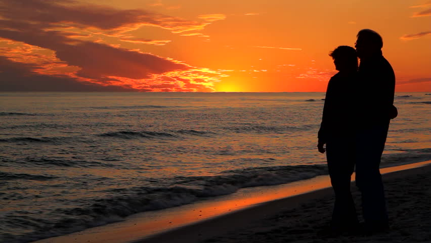 Retire man and woman stand together holding each other at the beach at sunset looking out toward the ocean. - HD stock video clip