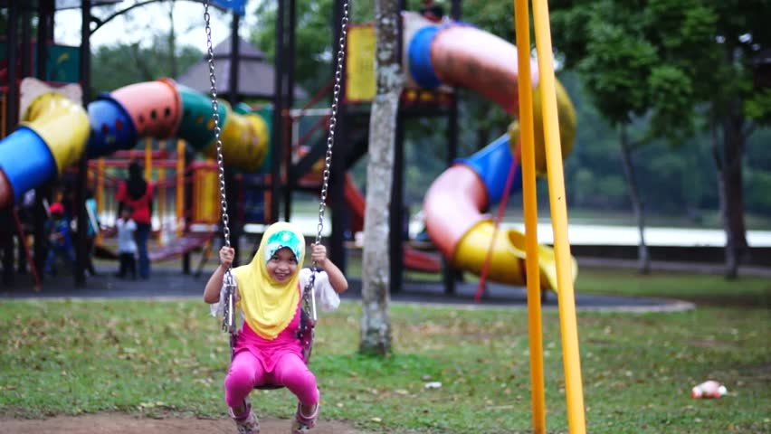 Young Muslim girl wearing scarf play swing happily at playground