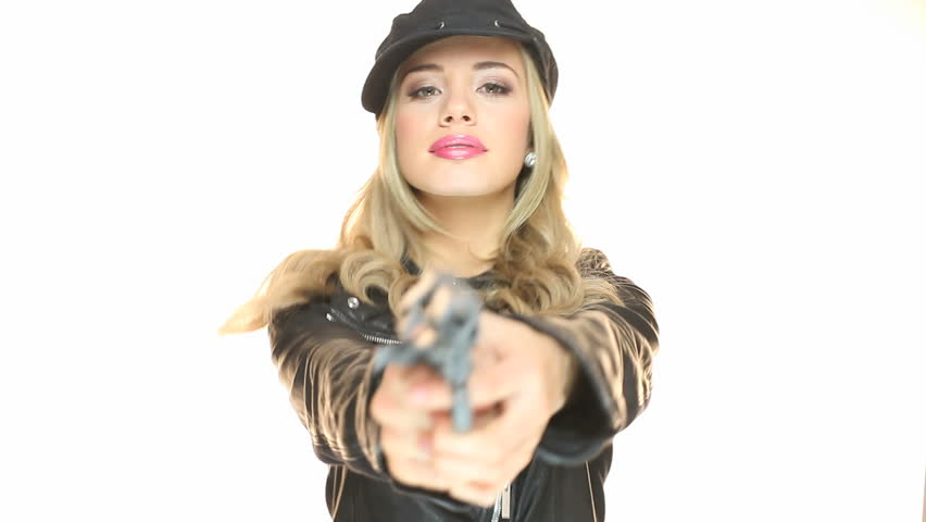 Staring straight down the muzzle of a gun at a beautiful blonde woman wearing a beret, focus to face - HD stock video clip