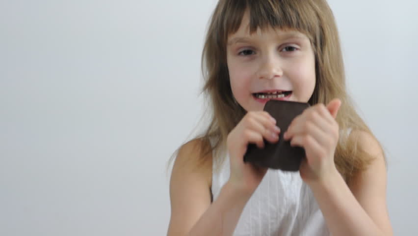 portrait of a little girl eating chocolate - HD stock footage clip