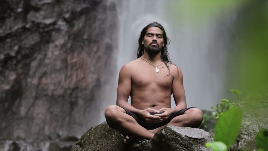 man doing sitting meditation at waterfall in the tropics - HD stock footage clip