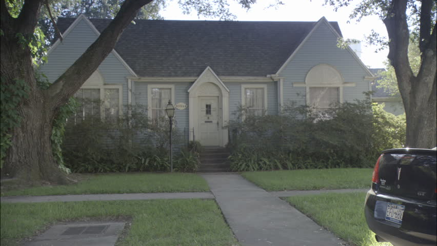 Day Static Slightly left quaint one story blue wood clapboard house white trim Lush green bushes trees Door starts open End parked black Pontiac car foreground Spring summer