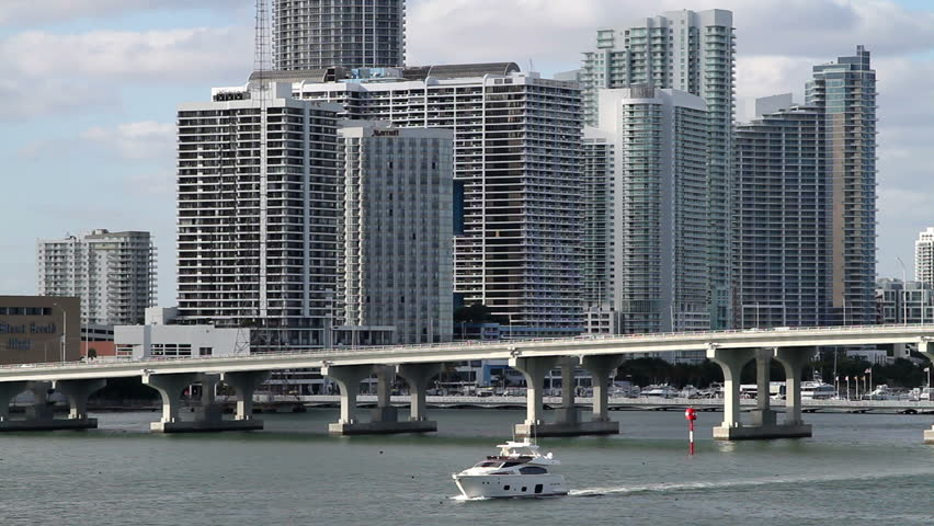 Cityscape, Miami skyline with bridge, from over the water angle. A boat enters