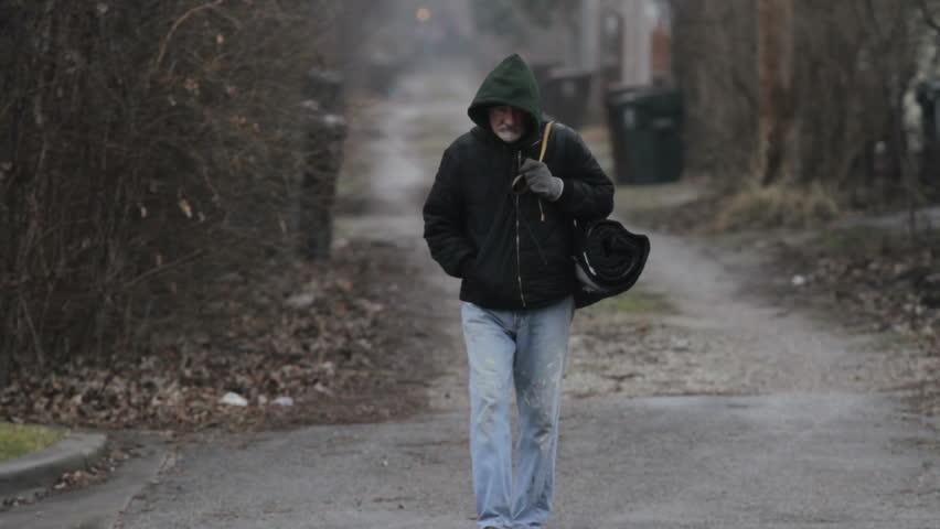 Homeless man walking in an alley