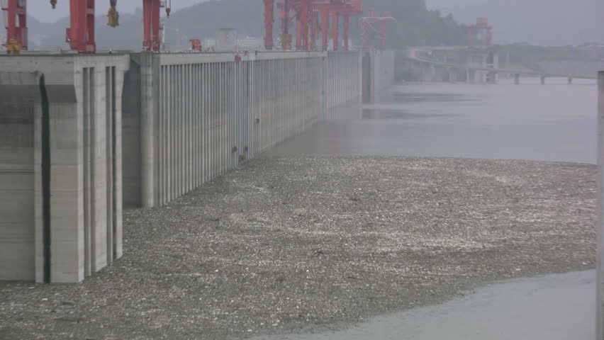Workers are cleaning up pollution in front of the walls of the Three Gorges Dam near Sandouping, China
