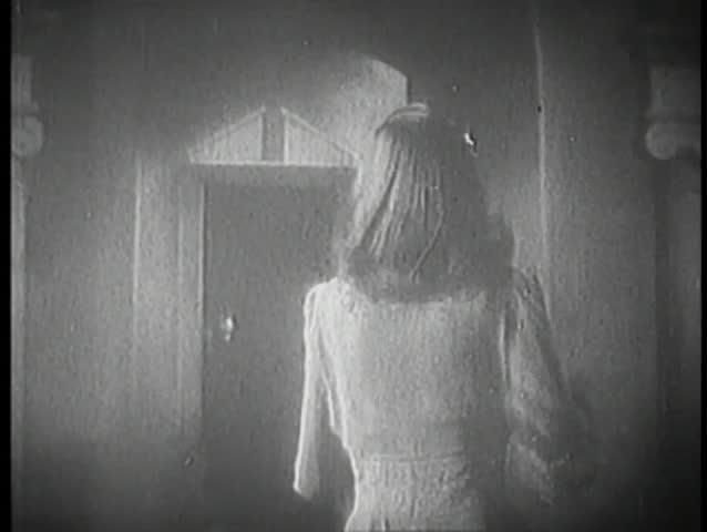Rear view of woman running towards door