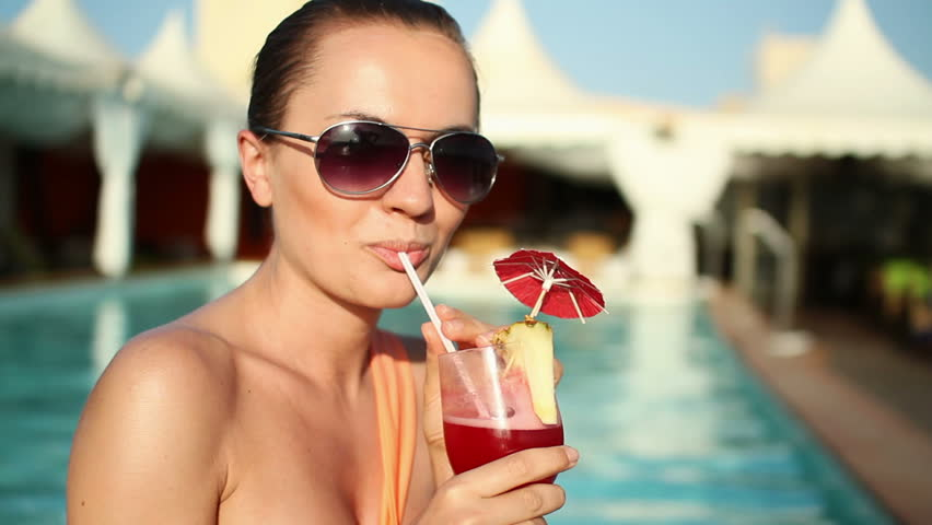 Happy woman drinking exotic cocktail by swimming pool