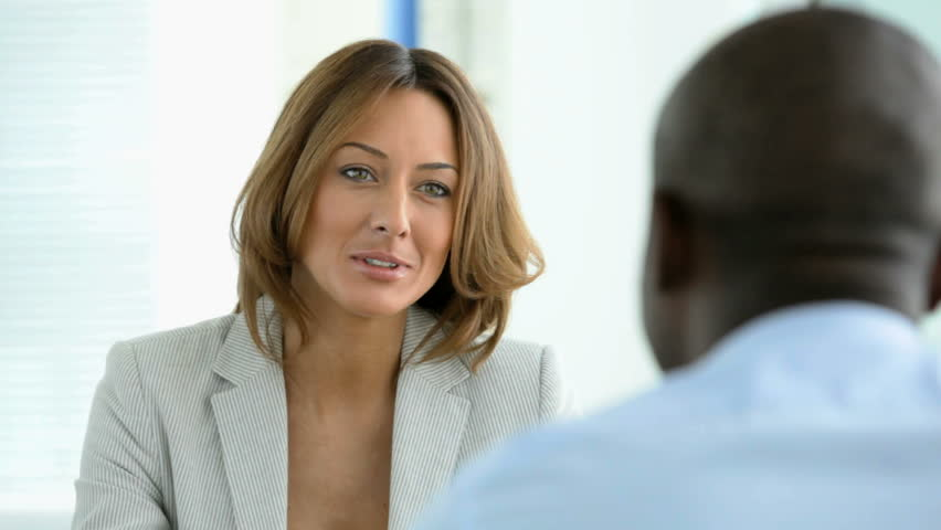 African-American man seen from his back taking part in a job interview or other business meeting talking to a smiling lady