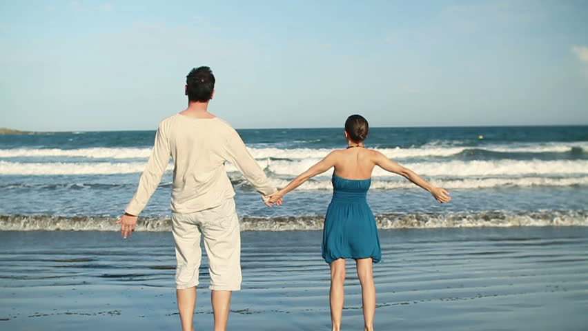 Young couple standing hand in hand on the beach, slow motion - HD stock footage clip