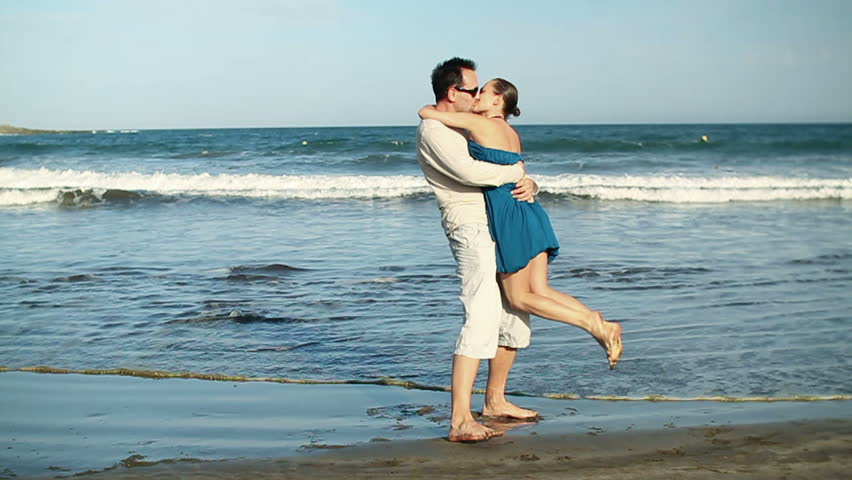 Happy young couple hugging each other at the beach, slow motion