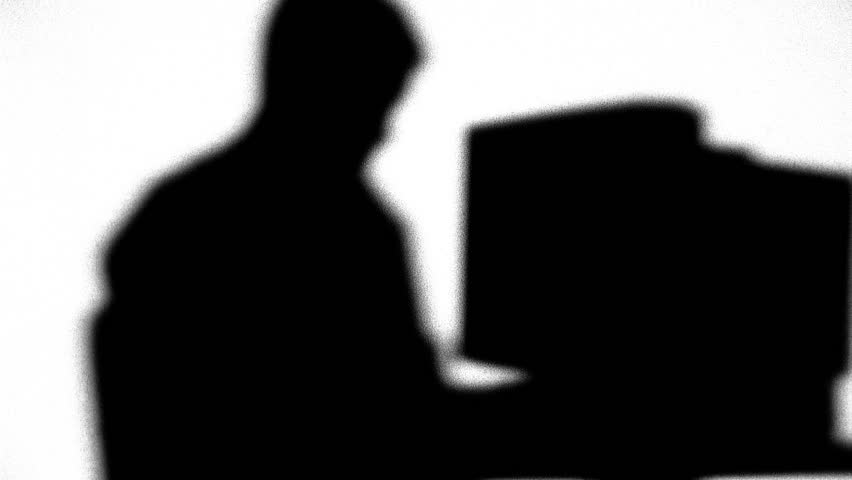 Silhouette of man typing on computer - HD stock video clip