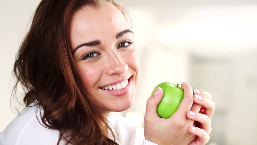 Joyful young woman eating green apple is healthy - HD stock footage clip