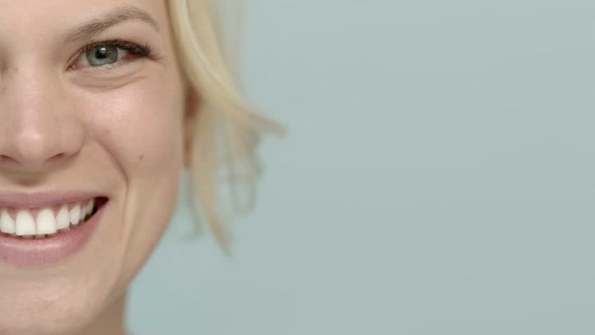 Beauty portrait, beautiful caucasian blonde woman smiling at camera. Cropped view, blue background, copy space