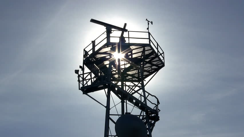 Marine traffic control radar tower silhouette with spinning antenna, anemometer and wind direction sensors against blue sky and wispy clouds  - HD stock footage clip
