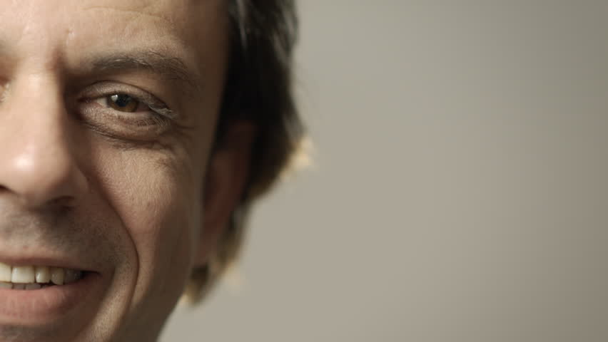 Portrait of happy caucasian adult man smiling at camera. Cropped view, grey background, copy space