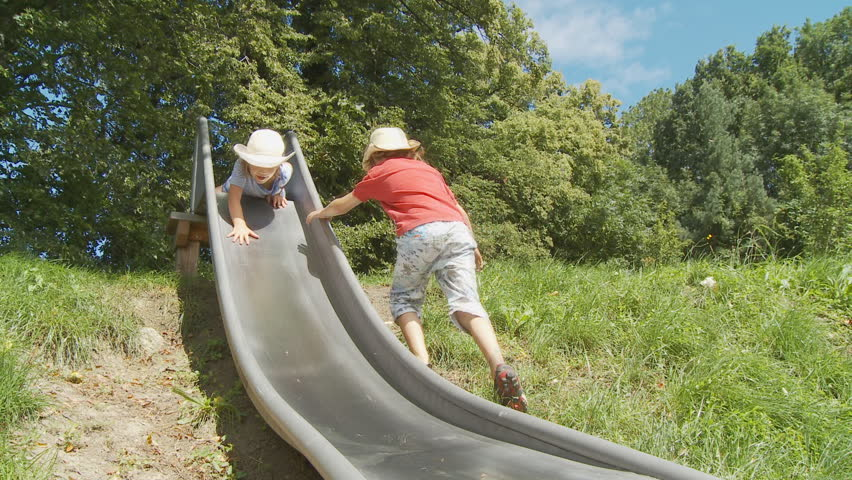 girl and boy with hats on slide - HD stock video clip
