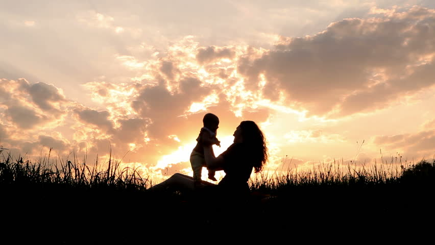 Silhouettes mother and baby sunset - HD stock video clip