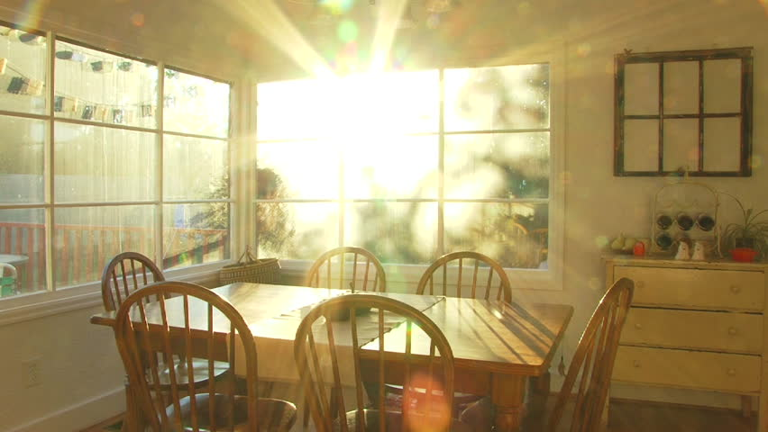 Bright sunset shines through window of dining room at house time lapse.