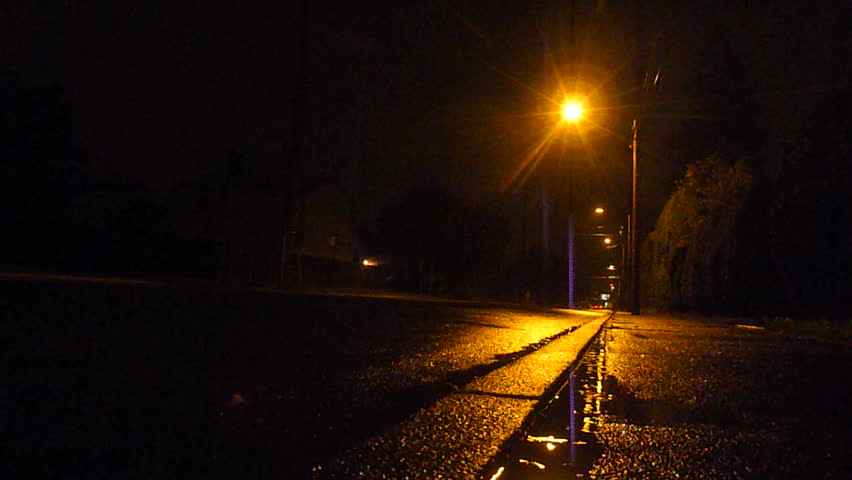 Mysterious person walks wet streetss at night in rain storm.