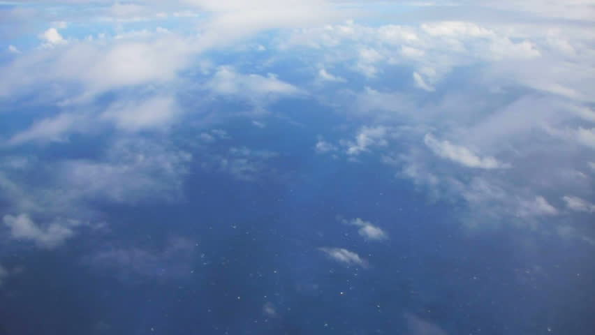 Flying in airplane over Pacific ocean dropping in altitude flying through clouds