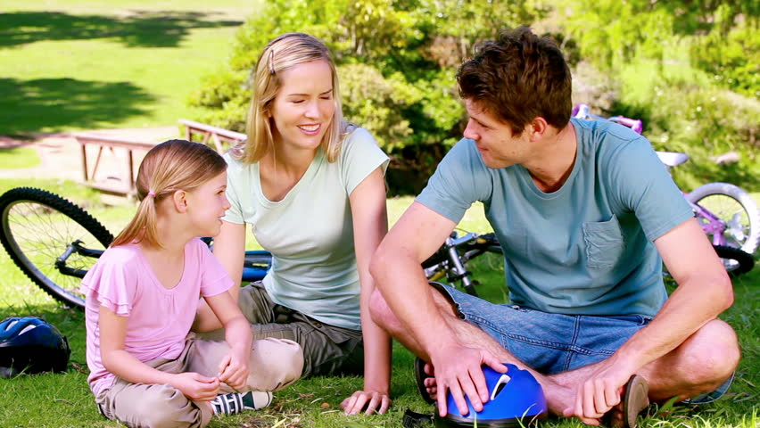 Girl with her parents with bikes sitting in a park - HD stock video clip