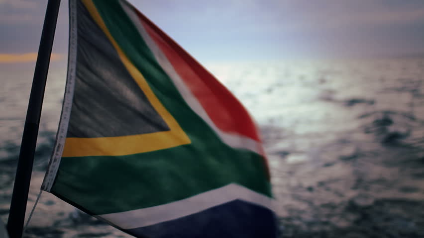 The South African flag blowing in the wind on a traveling motor boat in Cape Town, South Africa. - HD stock footage clip
