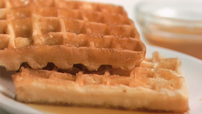 Maple syrup flowing in super slow motion on waffles