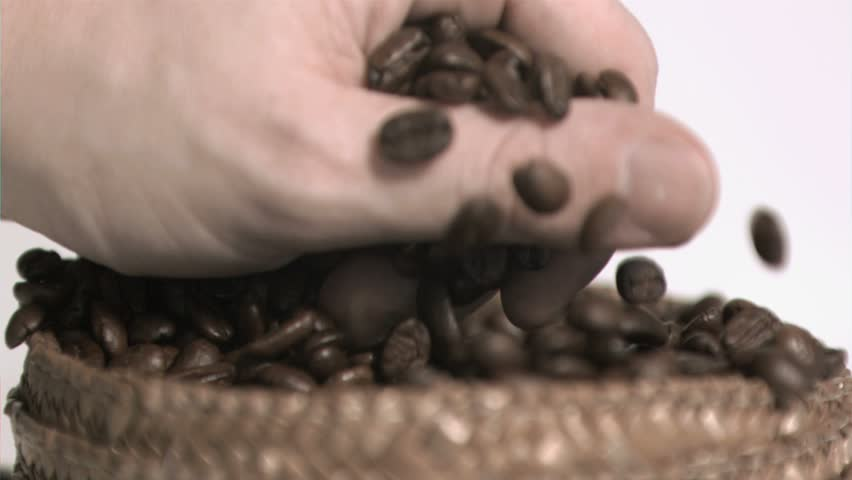 Coffee beans in super slow motion being held against a white background