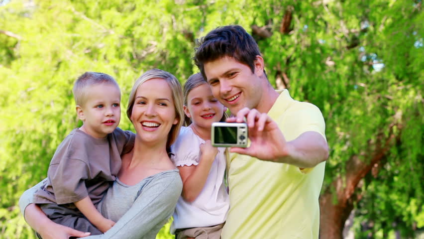 Family taking a picture with a digital camera in a park - HD stock video clip