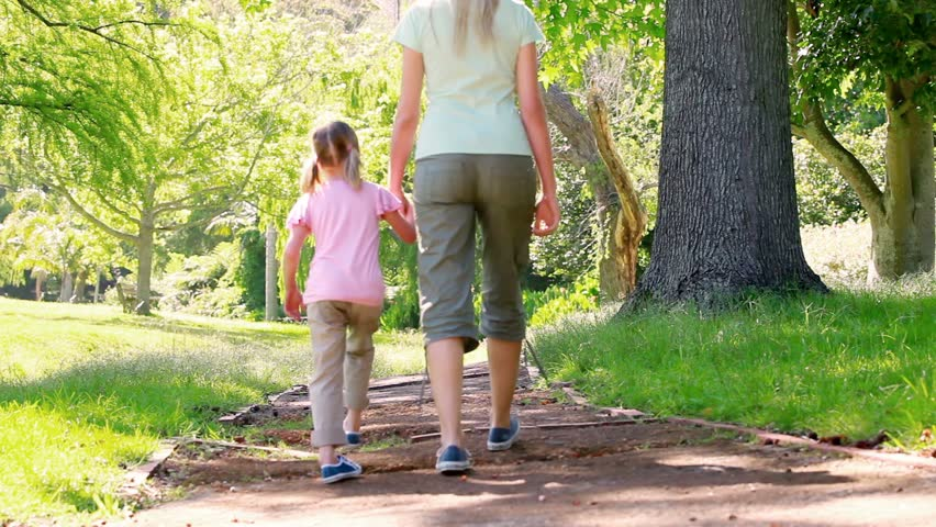 Mother and daughter walking together in a park - HD stock video clip