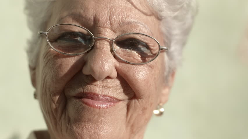 Senior portrait, happy old woman with eyeglasses smiling and looking at camera