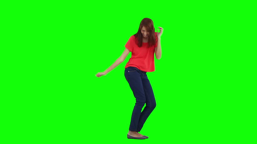 A happy woman is dancing on her own against a green background | Shutterstock HD Video #2371505