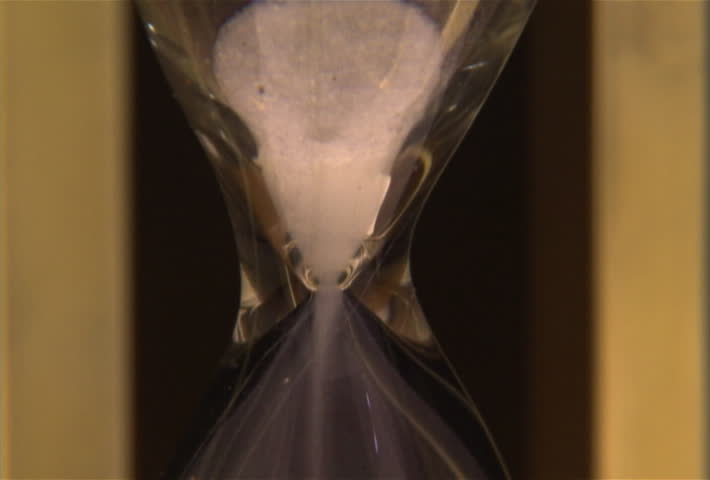 Sand slips through hourglass - SD stock footage clip