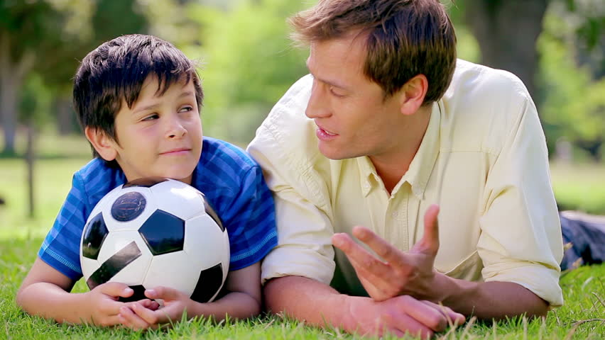 Happy father and son lying on the grass with a soccer ball in the countryside - HD stock footage clip
