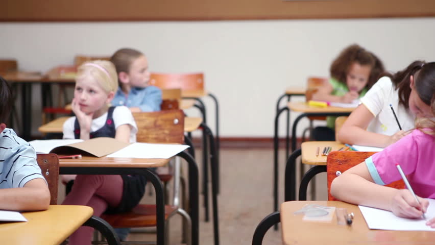 Pupils sitting at desks are working in a classroom - HD stock footage clip