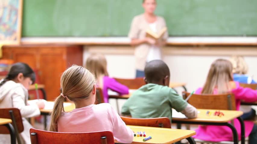 Cute children raising their fingers in the classroom
