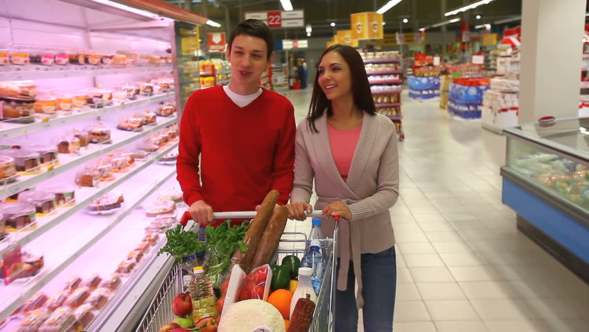 Young people doing shopping together in a modern big supermarket
