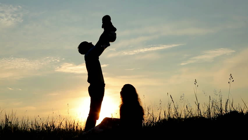 Happy family: father, mother and baby playing at sunset. Silhouettes - HD stock footage clip