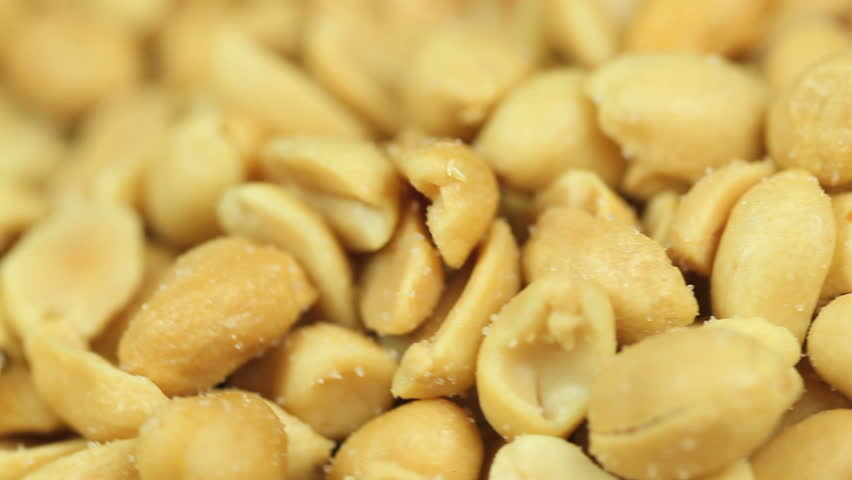 Closeup shot of a pile of salty peanuts rotating in a seamless loop, selective focus, to be used as a food background - HD stock video clip