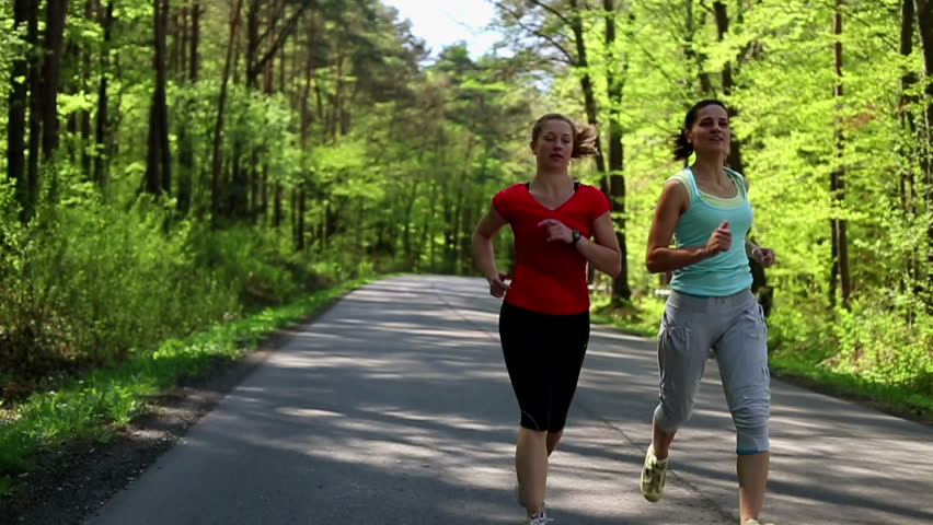 Two happy woman jogging in the forest, slow motion - HD stock video clip