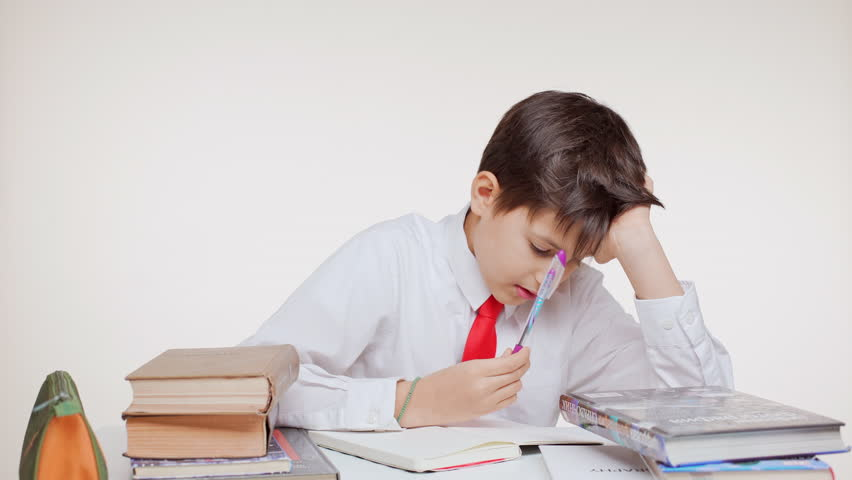 Young Caucasian kid school boy in red tie sitting at table learning writing surrounded by books on white background | Shutterstock HD Video #24240542