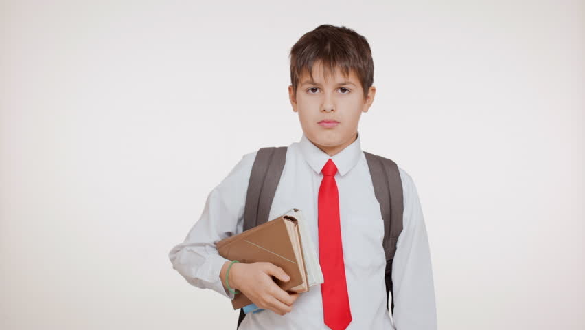 Young school Caucasian kid in red tie with rucksack and book standing on white background swowing ok than thumb down | Shutterstock HD Video #24240551