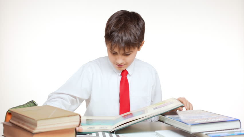 Young school kid with red tie sitting at table with books and atlas playing with cube on white background in slowmotion | Shutterstock HD Video #24255140