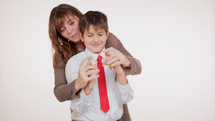 Young school kid in red tie standing on white background with his mother smiling playing pointing at camera | Shutterstock HD Video #24255158